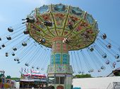 stock photo of carnival ride  - a swinger ride at a carnival on a beautiful day - JPG