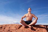 Muscular man meditating on red rocks