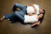stock photo of young girls  - Sexy young happy casual couple relaxing on the floor - JPG