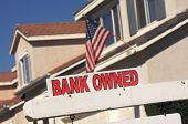 Bank Owned Real Estate Sign and House with American Flag in the Background.