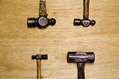stock photo of peen  - four old hammers showing hard use on brown background with room for logo or text - JPG