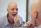 A beautiful cancer survivor applying makeup and getting ready to go out.