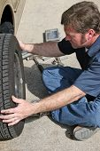 An auto mechanic removing a car tire.