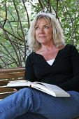 A beautiful, mature woman reading an inspirational book on her porch swing.