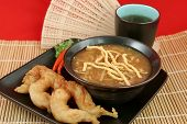 A bowl of hot & sour soup with chow mein noodles, fried fantail shrimp and hot tea.