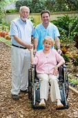 Disabled senior woman and her husband with a male nurse on the grounds of an assisted living facilit