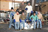 A group of metal workers posing with their supervisor in a scrap metal car.