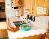 Salad and cutting board with veggies in the compact kitchen of a recreational vehicle.
