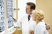 Doctor or chiropractor discussing the results of a cat scan of the spine with an elderly patient.