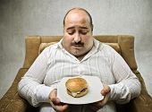 Sad fat man looking at a hamburger on his dish