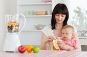 Gorgeous brunette woman pealing a banana while holding her baby on her knees in the kitchen