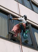 stock photo of cleaning service  - Window cleaner with bucket and cleaning equipment cleaning the windows on the outside of an office building hanging from a rope - JPG