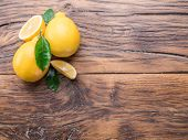 Ripe lemons and lemon leaves on wooden background. Top view. poster