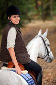 Young woman riding a beautiful white horse