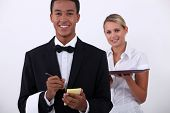a young latino well dressed waiter writing order and a young blonde waitress holding a platter