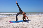 Woman Doing Yoga Exercise One Leg Full Wheel Pose On Beach