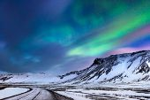 Beautiful landscape of the northern lights over hight mountains covered with snow,  Aurora Borealis, poster