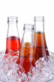 Three Open Soda Bottles in Glass Ice Bucket isolated over white