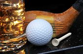 Antique Golf Club with Ball, Tee and Drink on Black Background