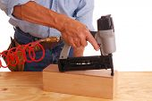 Carpenter with nail gun isolated over white