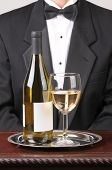 Waiter wearing a tuxedo with a White Wine Bottle With Blank Label and Glass on Silver Tray and Wood