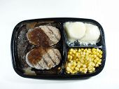 stock photo of frozen tv dinner  - A salisbury steak dinner still frozen before cooking - JPG