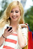 picture of mobile-phone  - Woman with shopping bags using mobile phone - JPG