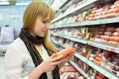 Blonde girl wearing scarf chooses sausage in large store; shallow depth of field