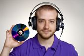 Young disk jockey holding a compact disc.Young man using headphones.
