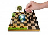 Hand Playing chess game with Silhouettes of business people vs nature (tree,earth,Wind turbines,flow