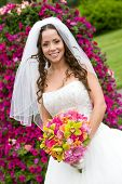 A bride with a bouquet in red, pink, green, and orange
