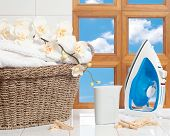 picture of laundry  - Housework concept with fresh laundry and iron against a window with blue sky - JPG
