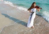 Junge attraktive Frau Geigenspiel auf Meer Hintergrund