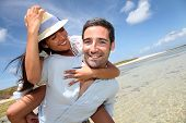 stock photo of piggyback ride  - Lovers enjoying sunny day at the beach - JPG
