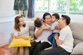 Side View Of Asian Granddaughter And Grandson Pecking Grandfather On His Cheek With Asian Father And poster