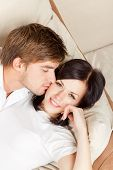 stock photo of kissing couple  - beautiful young couple sitting on a sofa - JPG