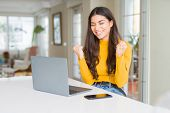 Young woman using computer laptop very happy and excited doing winner gesture with arms raised, smil poster