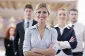 foto of seminar  - business woman standing with her staff in background at modern bright office conference room - JPG