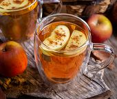 Closeup Of A Glass Mug Of Apple Cider With Apple Slices On A Rustic Wooden Surface poster