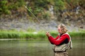 Fly Angler Or Fly Fisher Is Fishing On The Wild River Use The Fly Fishing. poster