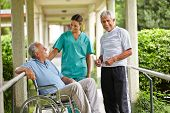 Two happy senior people taking to a nurse in a nursing home