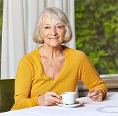 Smiling senior woman drinking a cup of coffee in a retirement home