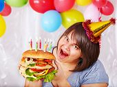 Woman eating hamburger at birthday at home.