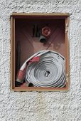picture of retarded  - public firefight equipment with hose and faucet in a plastered wall - JPG