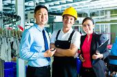 Chinese Shift supervisor or foreman, together with the owner or CEO and the Manager, standing proud