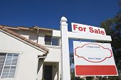 Low angle view of house with 'For Sale' sign