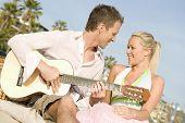 Young man serenading his girlfriend while playing guitar