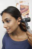 picture of otoscope  - Female doctor doing ear examination with otoscope on patient - JPG