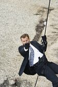 Man in suit aiming handgun while rappelling down the rope