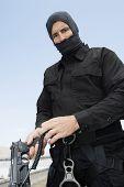 Commando standing with handgun on military training poster
